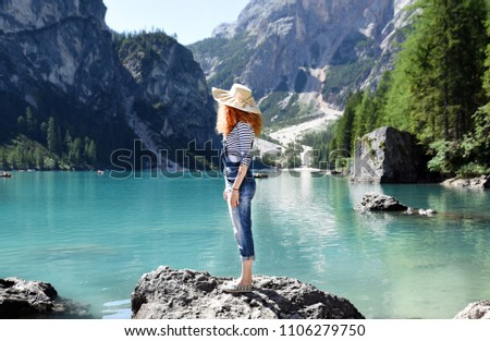 Young girl with red hair, dungarees, striped shirts and hat looks at the horizon above the rock of an alpine lake. Woman on vacation shooting in profile while enjoying the view inside the wild nature. #1106279750