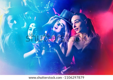 Dance party with group people dancing. Women and men have fun in night club. Back light on girls hair. People in brilliant suits. Toning and blur for background. Youth trends. Royalty-Free Stock Photo #1106297879