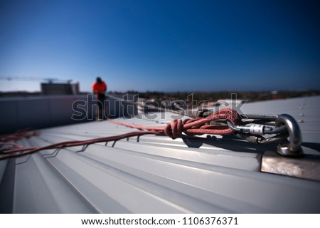 Rope access height safety carabiners connecting with figure of eight knots rigging, clipping into roof fall arrest and fall restraint anchor point systems ready to ascending, construction site Sydney Royalty-Free Stock Photo #1106376371