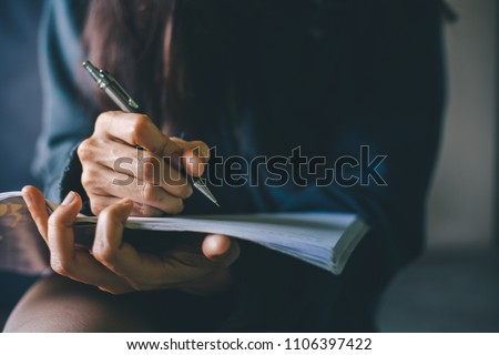 soft focus.hand high school or university student in casual holding pencil writing on paper answer sheet.sitting on lecture chair taking final exam or study attending in examination room or classroom Royalty-Free Stock Photo #1106397422