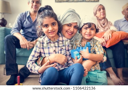 Muslim family relaxing and playing at home Royalty-Free Stock Photo #1106422136