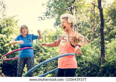 Senior woman exercising with a hula hoop Royalty-Free Stock Photo #1106439377