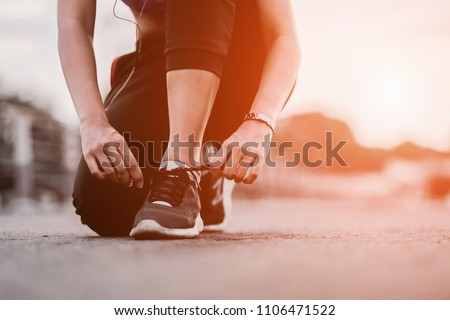Running shoes - closeup of woman tying shoe laces. Female sport fitness runner getting ready for jogging outdoors on way #1106471522