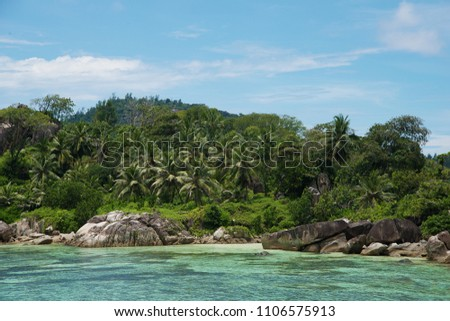 Beautiful view of the Indian Ocean from the island of Mae, Seychelles.  On the ocean lie huge stones.  Evergreen vegetation is in the foreground. #1106575913