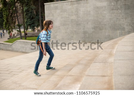 A schoolboy with a knapsack behind his back rises the steps #1106575925