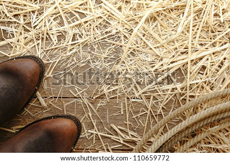 American West rodeo traditional roper leather cowboy boots and authentic lariat lasso loop on aged wood barn floor covered with hay straw in an old ranch barn #110659772