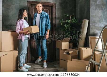 happy young couple with lot of boxes moving into new home #1106680034