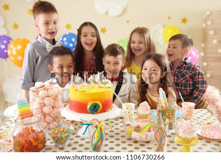 Cute children celebrating birthday at table indoors #1106730266