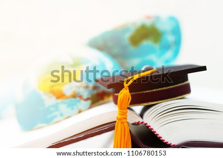 Graduate or Education knowledge learning study abroad concept : Graduation cap on opening textbook with blur of america australia earth world globe model map in Library room of campus, Back to School  #1106780153