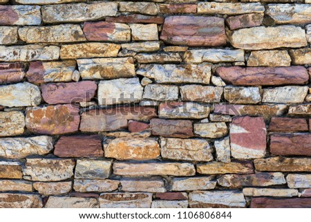 texture a closeup of a fragment of a stone wall or a part of a stone fence for a background #1106806844