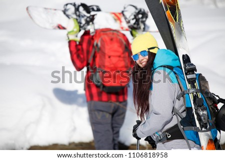 Photo of man and woman skiing down snow hill in winter #1106818958
