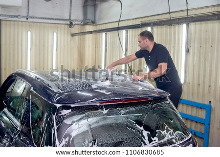 A man washes a blue car. Thorough washing of the body with foam and a high-pressure apparatus #1106830685
