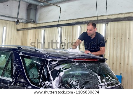 A man washes a blue car. Thorough washing of the body with foam and a high-pressure apparatus #1106830694