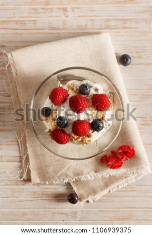 Raspberries, blueberries, cereals and yogurt in a glass bowl on sackcloth and wooden slats. Healthy breakfast for a healthy life. Vertical image view from above. #1106939375