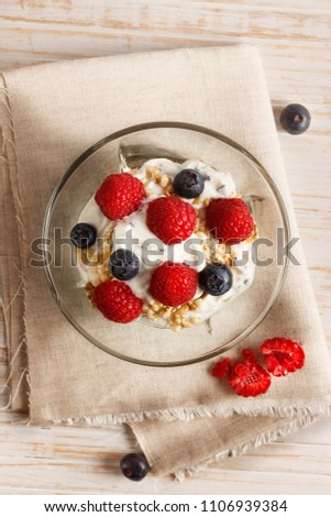Raspberries, blueberries, cereals and yogurt in a glass bowl on sackcloth and wooden slats. Healthy breakfast for a healthy life. Vertical image view from above. #1106939384