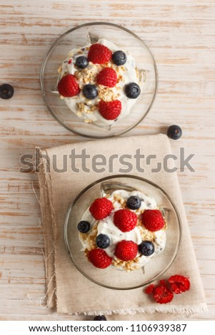 Raspberries, blueberries, cereals and yogurt in a glass bowl on sackcloth and wooden slats. Healthy breakfast for a healthy life. Vertical image view from above. #1106939387