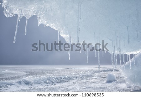 outdoor view of frozen baikal lake in winter with icicles on foreground Royalty-Free Stock Photo #110698535