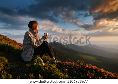 woman traveler drinks coffee with a view of the mountain landscape. A young tourist woman drinks a hot drink from a cup and enjoys the scenery in the mountains. Trekking concept #1106988677