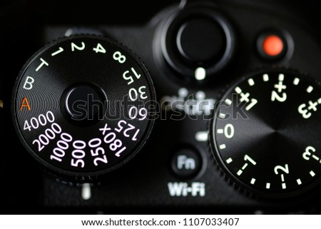 Shutter Speed dial of a digital camera in black background.
