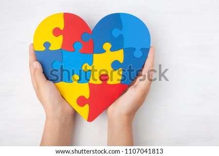 World Autism Awareness day, mental health care concept with puzzle or jigsaw pattern on heart with child's hands #1107041813
