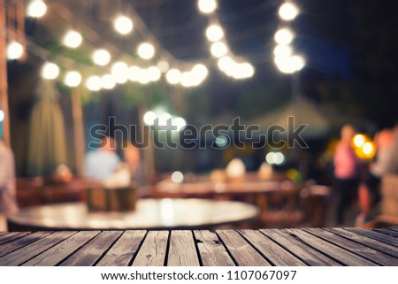 Empty wooden table top and blurred night street cafe interior #1107067097