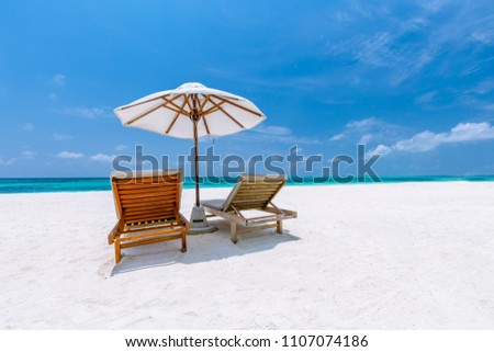 Perfect beach banner. White sand and romantic couple and honeymoon concept with two sun loungers and umbrella on white sand under blue sky #1107074186