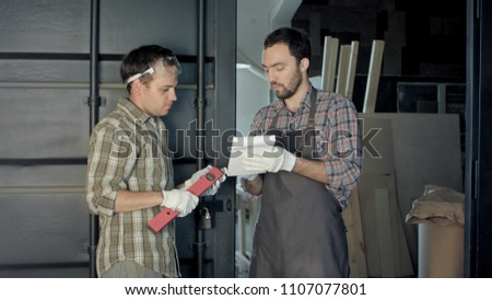 Two woodworkers discussing the process of making wood products. #1107077801