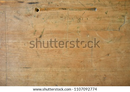 An abstract image of an old wooden school desk top.  #1107092774