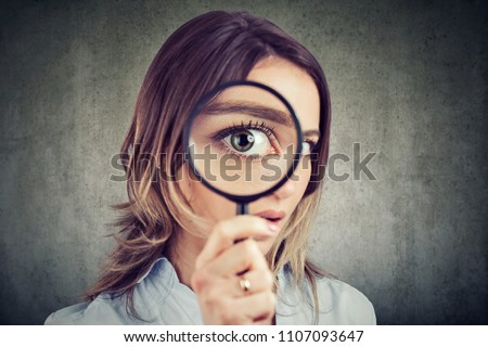 Curious young woman looking through a magnifying glass  Royalty-Free Stock Photo #1107093647