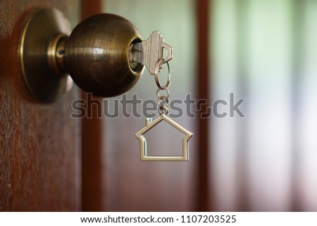 Home key with metal house keychain in keyhole, property concept #1107203525