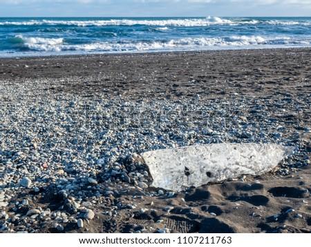 Ice pieces, glitter like diamonds, on black sand beach in winter season in Iceland, under cloudy blue sky #1107211763