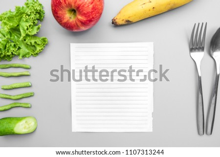 Fruits and Vegetables concept such as Apple, Banana, cucumber, lettuce, yard long bean and notepad in the middle with spoon and fork on grey background. #1107313244