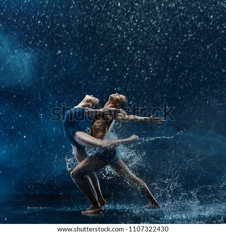 The couple of ballet dancers dancing under water drops and spray. Young caucasian and afro american models. Man and woman dancing together. Ballet and contemporary choreography concept. Art photo Royalty-Free Stock Photo #1107322430