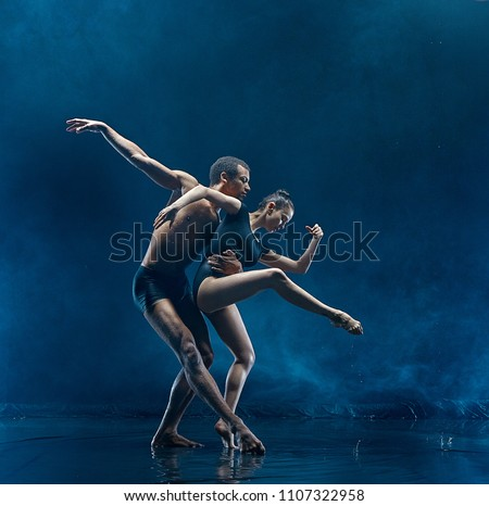 The couple of ballet dancers dancing under water drops and spray. Young caucasian and afro american models. Man and woman dancing together. Ballet and contemporary choreography concept. Art photo Royalty-Free Stock Photo #1107322958