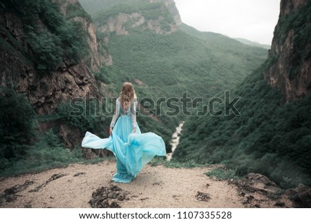 Beautiful blond color hair lady on the very brink of precipice. Lady in long dress with big mountains. Nice view of canyon and river in mountaing.  #1107335528