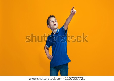 The teen boy pointing to camera, half length portrait on orange studio background. The human emotions, facial expression concept. Front view. Trendy colors #1107337721