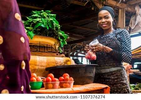 a girl selling tomatoes and vegetables in a typical local african market #1107376274