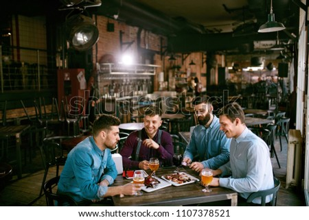 Men In Pub Drinking Beer And Eating Food #1107378521