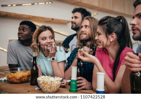 multiethnic group of friends watching football match at bar with fan horns, chips, popcorn, beer and soccer ball  #1107422528