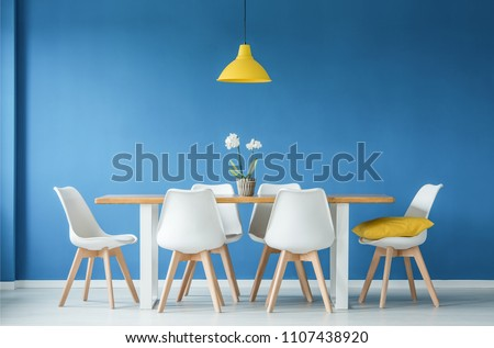 Blue dining room interior with a big table, white chairs and yellow chandelier