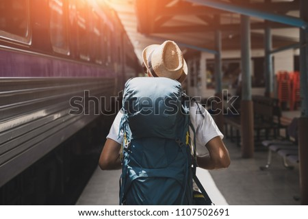 Young asian traveler with backpack in the railway, Backpack and hat at the train station with a traveler, Travel concept #1107502691