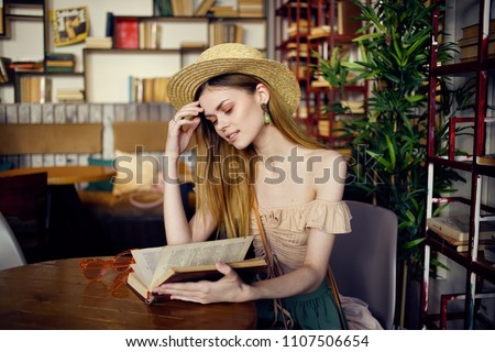 woman in a cafe reading a book                            #1107506654