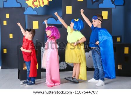 Cute children in superhero costumes against comic strip themed decoration