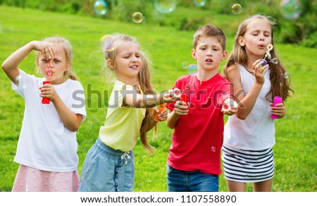 Four cheerful smiling kids in school age sitting together in park and blowing soap bubbles #1107558890