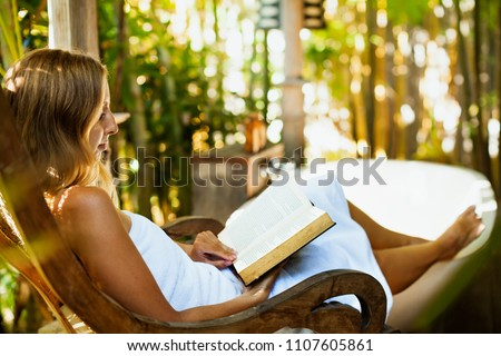 Attractive girl sit at rocking chair drinking morning coffee, reading romance in paper book. Relaxing woman fill bath tub in Boho style outside bathroom in luxury villa on summer tropical vacation. #1107605861