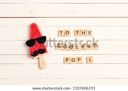 Father's Day greeting card with funny ice cream and wooden tiles comic text on white wooden background. To the coolest pop!