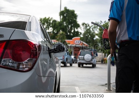 transportation and ownership concept - man pumping gasoline fuel in car at gas station #1107633350