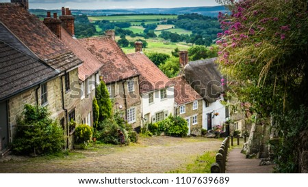 Old English limestone houses with thatched roofs with green fields countryside in the background. Gold Hill houses on a cloudy day behind flowers in Shaftesbury, Dorset, UK. Photo with selective focus Royalty-Free Stock Photo #1107639689