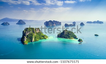 Surrounding Islands of Koh Yao Noi, Phuket, Thailand green lush tropical island in a blue and turquoise sea with islands in the background and clouds with sun beams shining through, drone aerial photo #1107675575