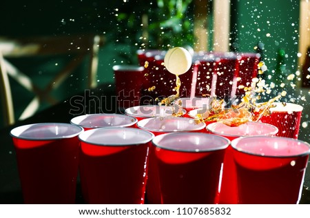 Cups and plastic ball for beer pong game on table #1107685832